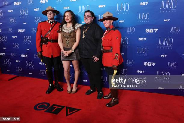 Quantum Tangle poses with RCMP officers as they arrive on the red carpet before the JUNO awards at the Canadian Tire Centre in Ottawa Ontario on...