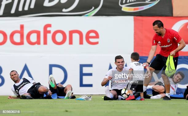 Quaresma and Pepe of Besiktas play with Tolgay Arslan's son Kian during the training session ahead of the Turkcell Super Cup football match between...