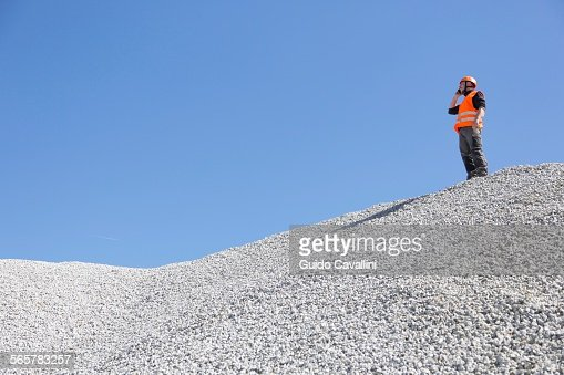 Quarry worker chatting on smartphone from quarry gravel mound