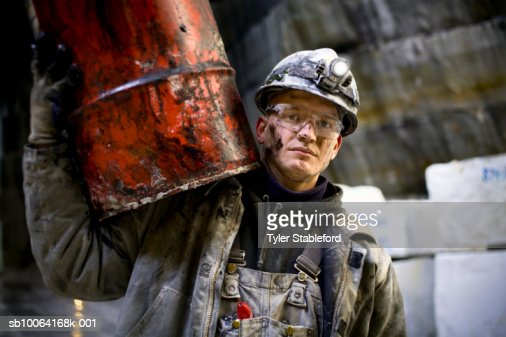 Quarryman carrying grease drum, portrait, close-up : Stock Photo