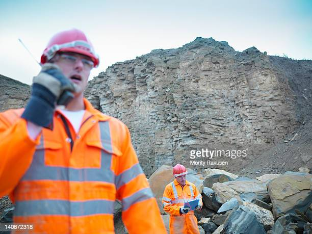 Quarryman using walkie talkie by cliff face of quarry