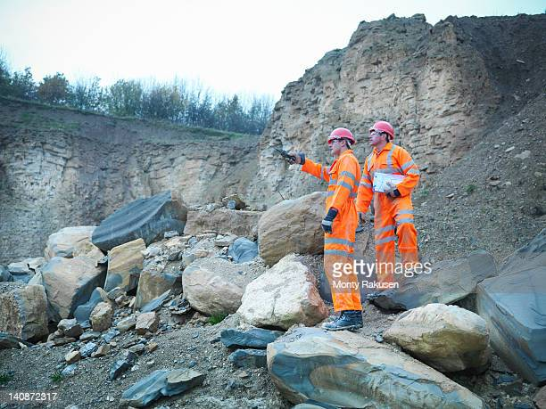 Quarrymen in discussion amid rocks and cliff face of quarry