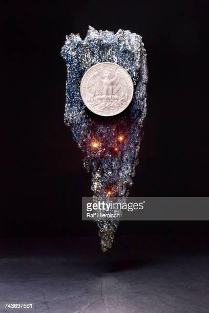 US quarter coin on shiny levitating stone against black background