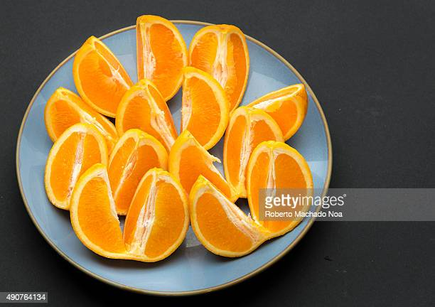 Quarter cut and unpeeled pieces of orange fruit arranged on a round blue plate in black background