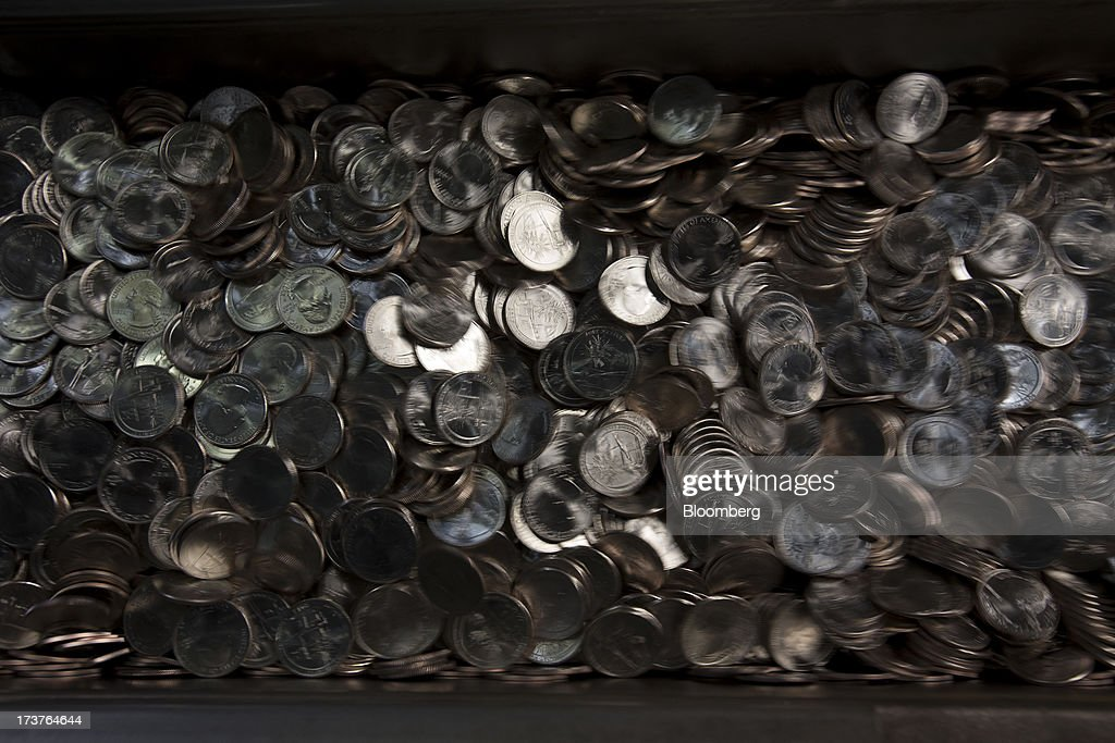 U.S. quarter dollar coins move down a conveyor belt after being pressed at the U.S. Mint in Philadelphia, Pennsylvania, U.S., on Wednesday, July 17, 2013. Some sources of declining inflation 'are likely to be transitory' and expectations for future price increases 'have generally remained stable,' Ben S. Bernanke, chairman of the U.S. Federal Reserve said in prepared remarks. Photographer: Scott Eells/Bloomberg via Getty Images