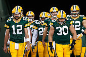 Quarterback Aaron Rodgers and fullback John Kuhn of the Green Bay Packers lead teammates onto the field before the NFL game against the Seattle...