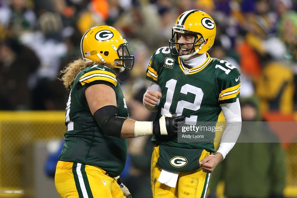 Quarterback Aaron Rodgers #12 and guard Josh Sitton #71 of the Green Bay Packers celebrate after fullback John Kuhn #30 scorers on a nine-yard catch and run in the third quarter against the Minnesota Vikings during the NFC Wild Card Playoff game at Lambeau Field on January 5, 2013 in Green Bay, Wisconsin.
