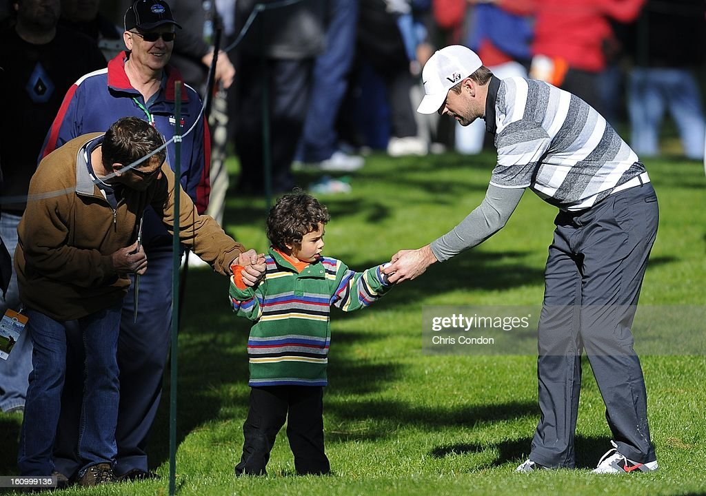 Quarterback Aaron Rodgers gives a golf ball to a young fan on the 8th hole during the second round of the AT&T Pebble Beach National Pro-Am at Spyglass Hill Golf Course on February 8, 2013 in Pebble Beach, California.