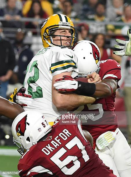 Quarterback Aaron Rodgers of the Green Bay Packer is sacked by outside linebacker Alex Okafor and cornerback Jerraud Powers of the Arizona Cardinals...