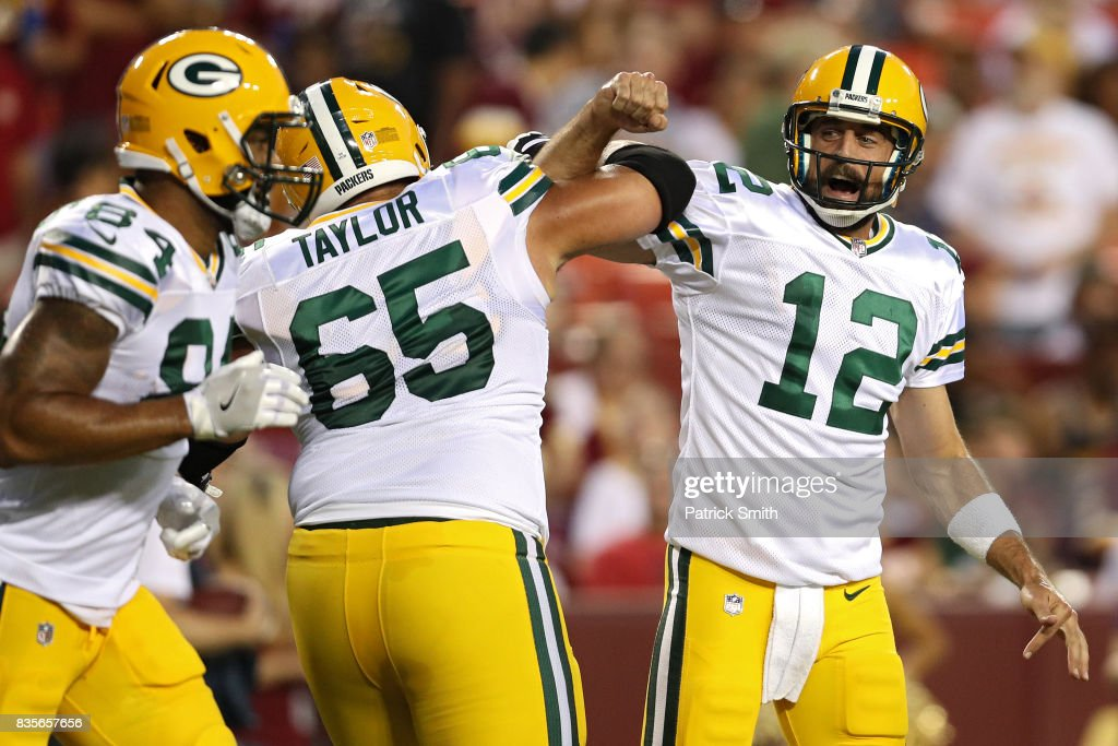 Quarterback Aaron Rodgers #12 of the Green Bay Packers celebrates a touchdown pass with teammate Lane Taylor #65 against the Washington Redskins in the first half during a preseason game at FedExField on August 19, 2017 in Landover, Maryland.