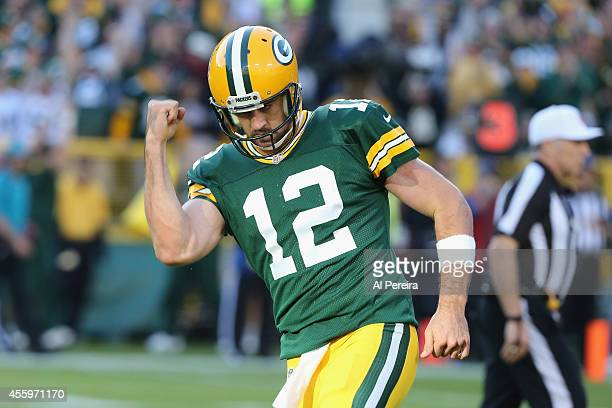 Quarterback Aaron Rodgers of the Green Bay Packers celebrates throwing a touchdown against the New York Jets at Lambeau Field on September 14 2014 in...