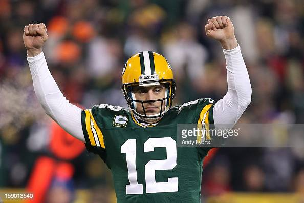 Quarterback Aaron Rodgers of the Green Bay Packers celebrates after fullback John Kuhn scores on a threeyard touchdown run in the second quarter...
