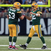 Quarterback Aaron Rodgers of the Green Bay Packers celebrates his 39 yard touchdown pass to wide receiver Randall Cobb of the Green Bay Packers with...