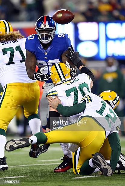 quarterback Aaron Rodgers of the Green Bay Packers fumbles the ball against defensive end Jason PierrePaul of the New York Giants in the second...