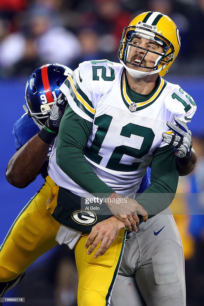 quarterback Aaron Rodgers #12 of the Green Bay Packers gets hit as he releases the ball by defensive end Justin Tuck #91 of the New York Giants at MetLife Stadium on November 25, 2012 in East Rutherford, New Jersey.