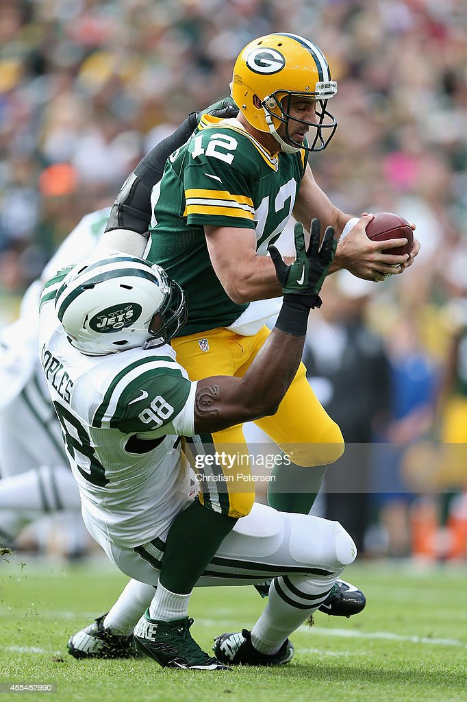 Quarterback Aaron Rodgers #12 of the Green Bay Packers is sacked by outside linebacker Quinton Coples #98 of the New York Jets in the first quarter during the NFL game at Lambeau Field on September 14, 2014 in Green Bay, Wisconsin.
