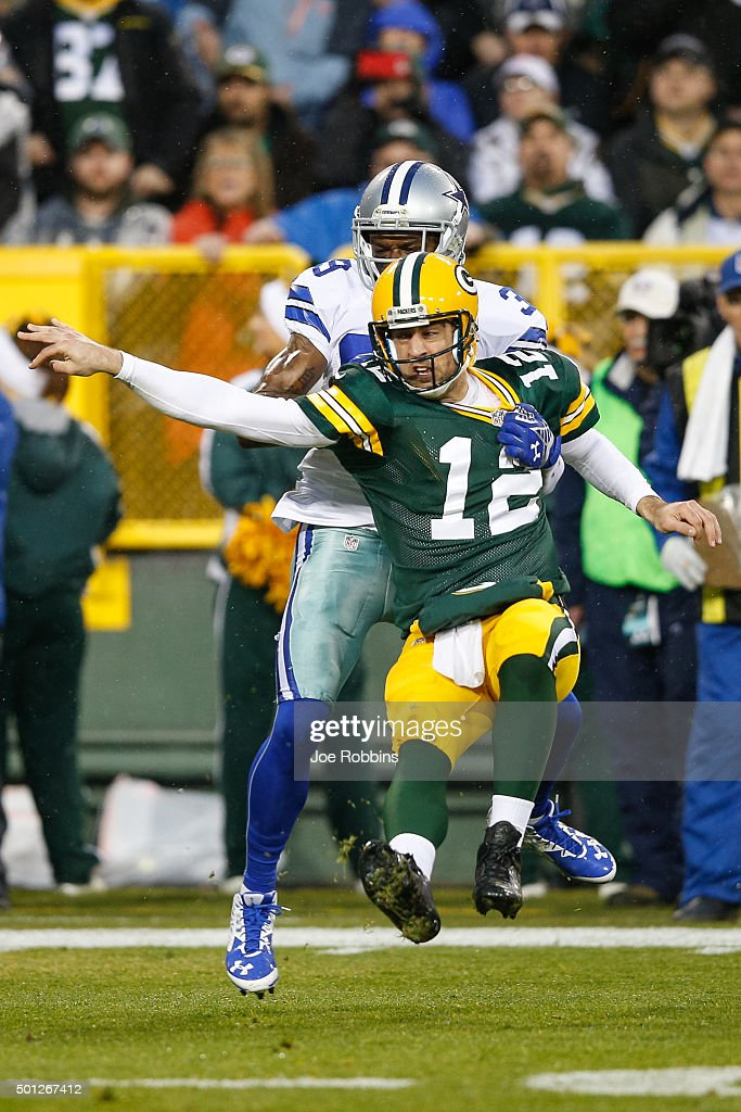 Quarterback <a gi-track='captionPersonalityLinkClicked' href=/galleries/search?phrase=Aaron+Rodgers+-+Quarterback+de+futebol+americano&family=editorial&specificpeople=215257 ng-click='$event.stopPropagation()'>Aaron Rodgers</a> #12 of the Green Bay Packers is tackled by <a gi-track='captionPersonalityLinkClicked' href=/galleries/search?phrase=Brandon+Carr&family=editorial&specificpeople=5357381 ng-click='$event.stopPropagation()'>Brandon Carr</a> #39 of the Dallas Cowboys in the first half at Lambeau Field on December 13, 2015 in Green Bay, Wisconsin. The Green Bay Packers defeated the Dallas Cowboys 28 to 7.