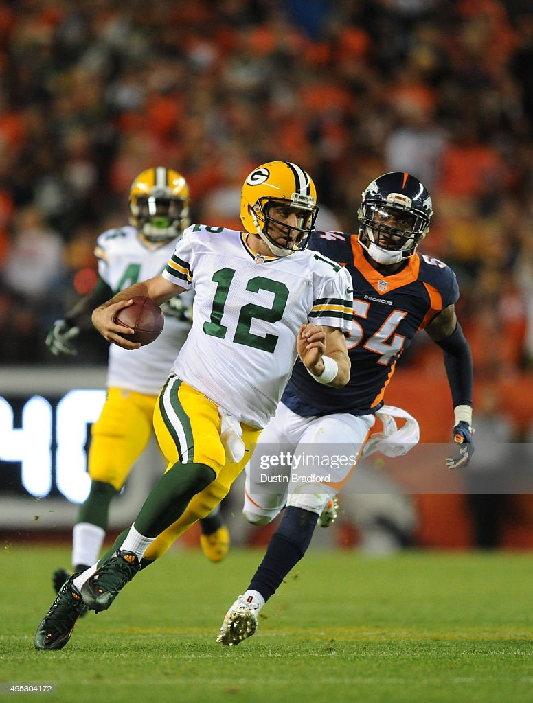 Quarterback Aaron Rodgers #12 of the Green Bay Packers runs the ball against Brandon Marshall #54 of the Denver Broncos in the third quarter at Sports Authority Field at Mile High on November 1, 2015 in Denver, Colorado.