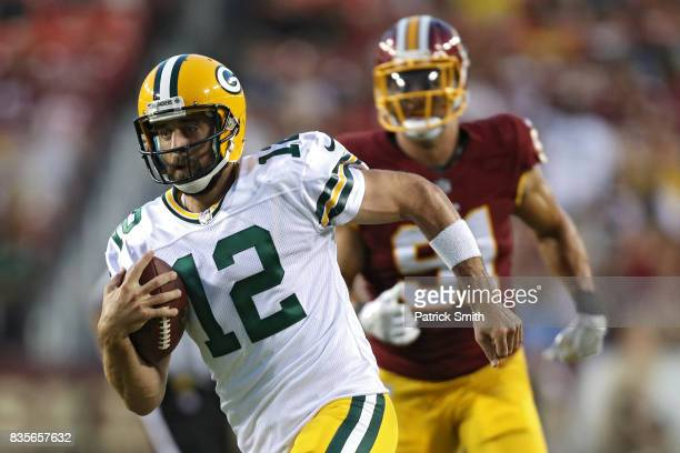 Quarterback Aaron Rodgers of the Green Bay Packers rushes with the ball against the Washington Redskins in the first half during a preseason game at...