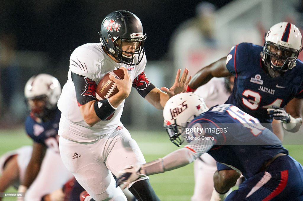 Quarterback Adam Kennedy #5 of the Arkansas State Red Wolves attempts to maneuver past safety Terrell Brigham #18 of the South Alabama Jaguars on November 2, 2013 at Ladd-Peebles Stadium in Mobile, Alabama. Arkansas State defeated South Alabama 17-16.