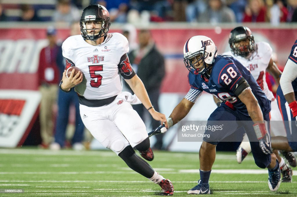 Quarterback Adam Kennedy #5 of the Arkansas State Red Wolves runs past linebacker Enrique Williams #28 of the South Alabama Jaguars on November 2, 2013 at Ladd-Peebles Stadium in Mobile, Alabama. Arkansas State defeated South Alabama 17-16.
