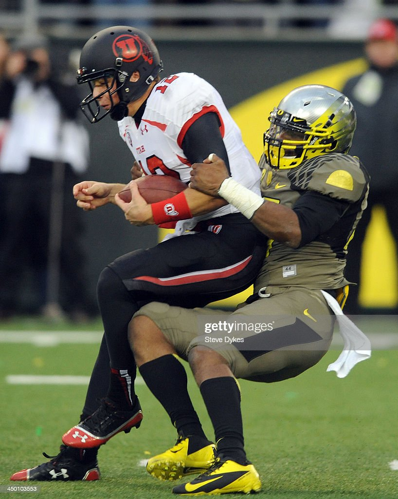 Quarterback Adam Schulz #12 of the Utah Utes is sacked by linebacker Boseko Lokombo #25 of the Oregon Ducks during the third quarter of the game at Autzen Stadium on November 16, 2013 in Eugene, Oregon.