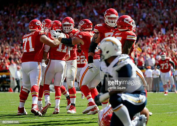Quarterback Alex Smith of the Kansas City Chiefs is congratulated by teammates after scoring a touchdown to win the game against the San Diego...