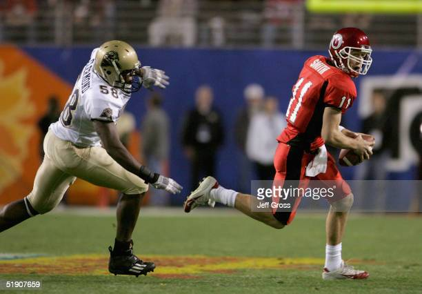 Quarterback Alex Smith of Utah runs for a nine yard gain chased by Joe Clermond of Pittsburgh in the first quarter of the Tostito's Fiesta Bowl at...