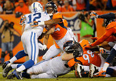 Quarterback Andrew Luck of the Indianapolis Colts is tackled by linebacker Brandon Marshall of the Denver Broncos for a loss of a yard on fourth down...