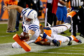 Quarterback Andrew Luck of the Indianapolis Colts reaches across the goal line for a secondquarter touchdown against the Denver Broncos at Sports...