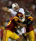 Quarterback Andrew Luck of the Stanford Cardinal is hit after throwing a pass by defensive linemen Wes Horton and Dajohn Harris of the USC Trojans at...