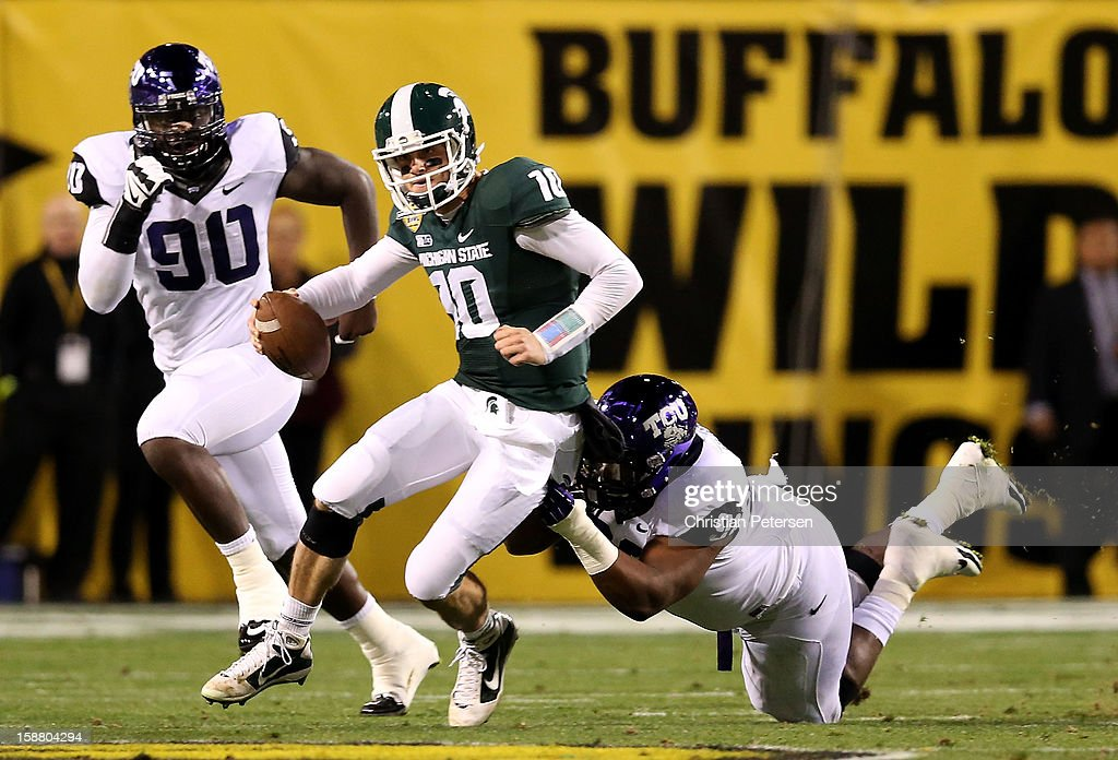 Quarterback Andrew Maxwell #10 of the Michigan State Spartans is sacked by defensive tackle Chucky Hunter #96 of the TCU Horned Frogs during the Buffalo Wild Wings Bowl at Sun Devil Stadium on December 29, 2012 in Tempe, Arizona.