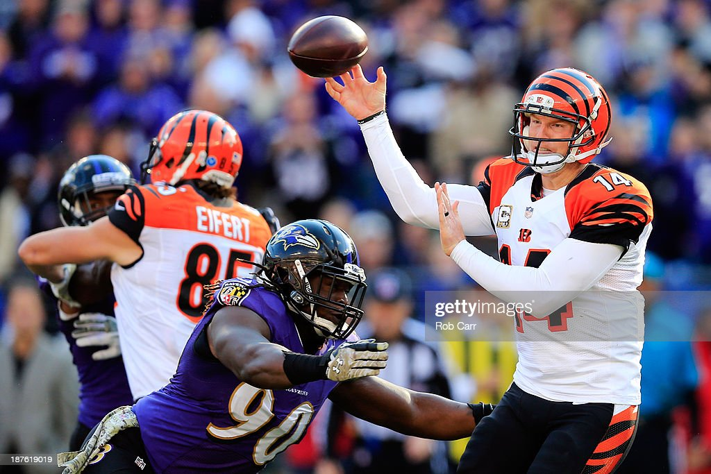 Quarterback <a gi-track='captionPersonalityLinkClicked' href=/galleries/search?phrase=Andy+Dalton+-+American+Football+Player&family=editorial&specificpeople=15271549 ng-click='$event.stopPropagation()'>Andy Dalton</a> #14 of the Cincinnati Bengals gets off a pass while being pressured by linebacker <a gi-track='captionPersonalityLinkClicked' href=/galleries/search?phrase=Pernell+McPhee&family=editorial&specificpeople=6393111 ng-click='$event.stopPropagation()'>Pernell McPhee</a> #90 of the Baltimore Ravens at M&T Bank Stadium on November 10, 2013 in Baltimore, Maryland.