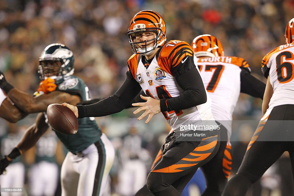 Quarterback <a gi-track='captionPersonalityLinkClicked' href=/galleries/search?phrase=Andy+Dalton+-+American+Football+Player&family=editorial&specificpeople=15271549 ng-click='$event.stopPropagation()'>Andy Dalton</a> #14 of the Cincinnati Bengals hands off during a game against the Philadelphia Eagles on December 13, 2012 at Lincoln Financial Field in Philadelphia, Pennsylvania. The Bengals won 34-13.
