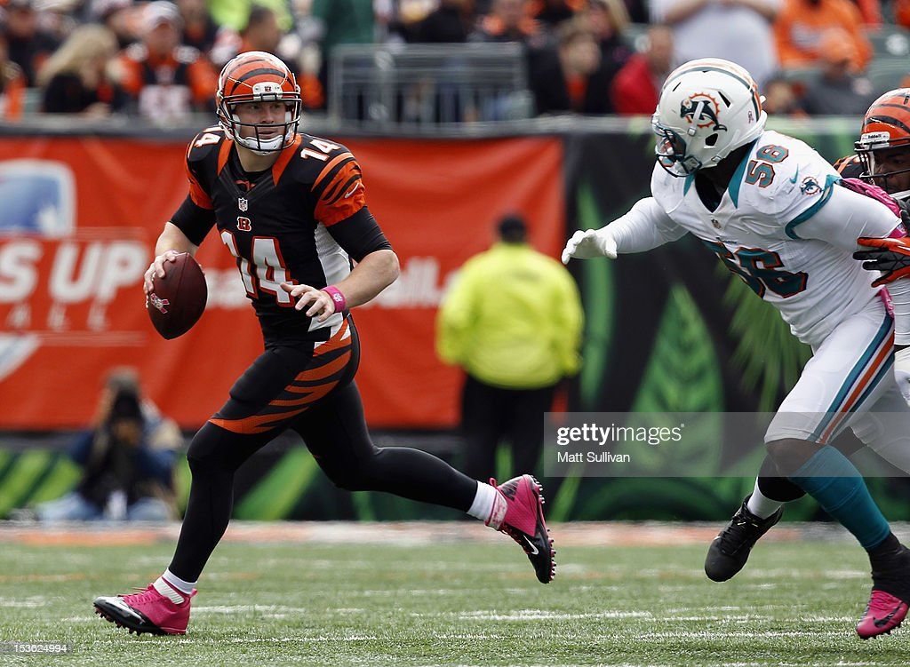 Quarterback <a gi-track='captionPersonalityLinkClicked' href=/galleries/search?phrase=Andy+Dalton+-+American+Football+Player&family=editorial&specificpeople=15271549 ng-click='$event.stopPropagation()'>Andy Dalton</a> #14 of the Cincinnati Bengals runs from linebacker Kevin Burnett #56 of the Miami Dolphins at Paul Brown Stadium on October 7, 2012 in Cincinnati, Ohio.