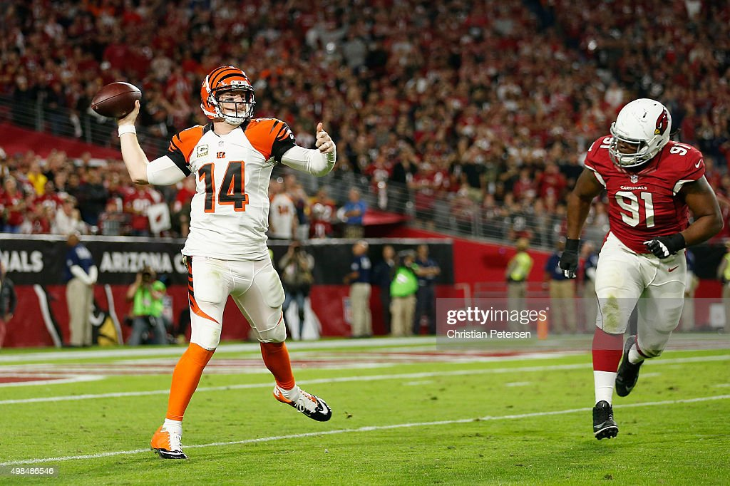 Quarterback Andy Dalton of the Cincinnati Bengals throws a pass under pressure from defensive tackle Ed Stinson of the Arizona Cardinals during the...