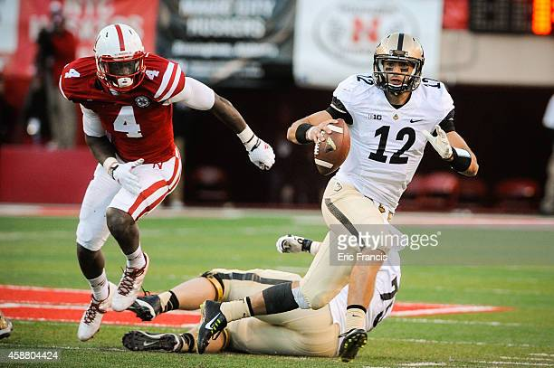 Quarterback Austin Appleby of the Purdue Boilermakers runs from defensive end Randy Gregory of the Nebraska Cornhuskers during their game at Memorial...