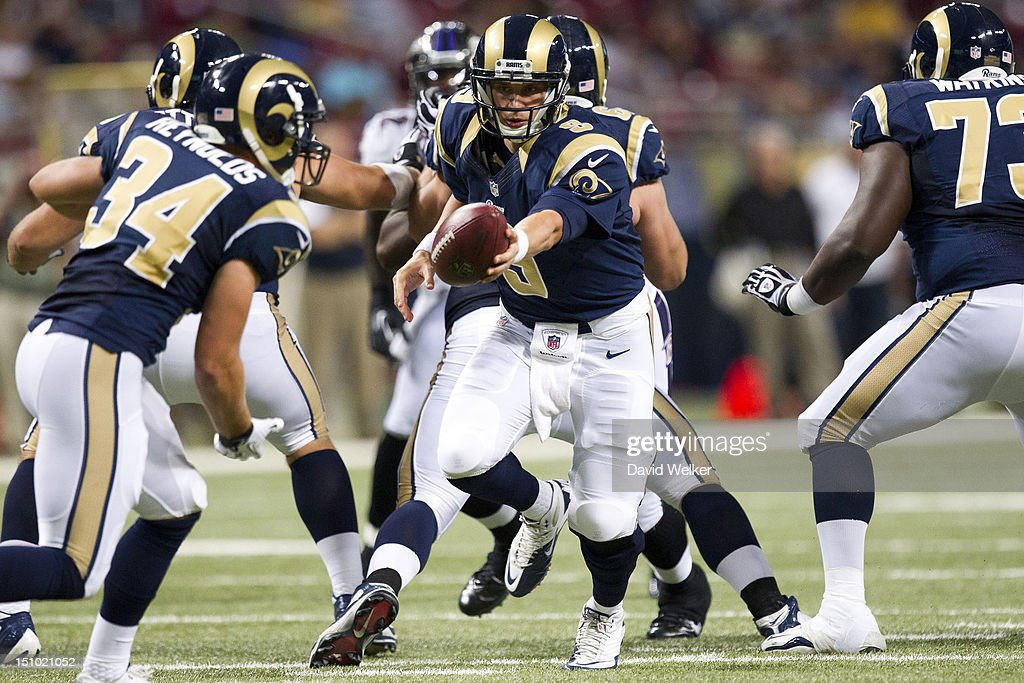 Quarterback <a gi-track='captionPersonalityLinkClicked' href=/galleries/search?phrase=Austin+Davis&family=editorial&specificpeople=1058943 ng-click='$event.stopPropagation()'>Austin Davis</a> #9 of the St. Louis Rams stretches to hand off the ball to running back Chase Reynolds #34 of the St. Louis Rams during the game against the Baltimore Ravens at the Edward Jones Dome on August 30, 2012 in St. Louis, Missouri. The St. Louis Rams defeated the Baltimore Ravens 31-17.