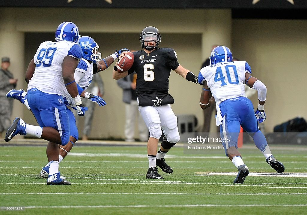 Quarterback Austyn Carta-Samuels #6 of the Vanderbilt Commodores is pressured by Donte Rumph #99 and Avery Williamson #40 of the Kentucky Wildcats at Vanderbilt Stadium on November 16, 2013 in Nashville, Tennessee.