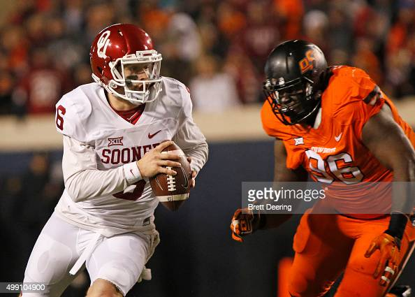 Quarterback Baker Mayfield of the Oklahoma Sooners scrambles under pressure from defensive tackle Vincent Taylor of the Oklahoma State Cowboys...
