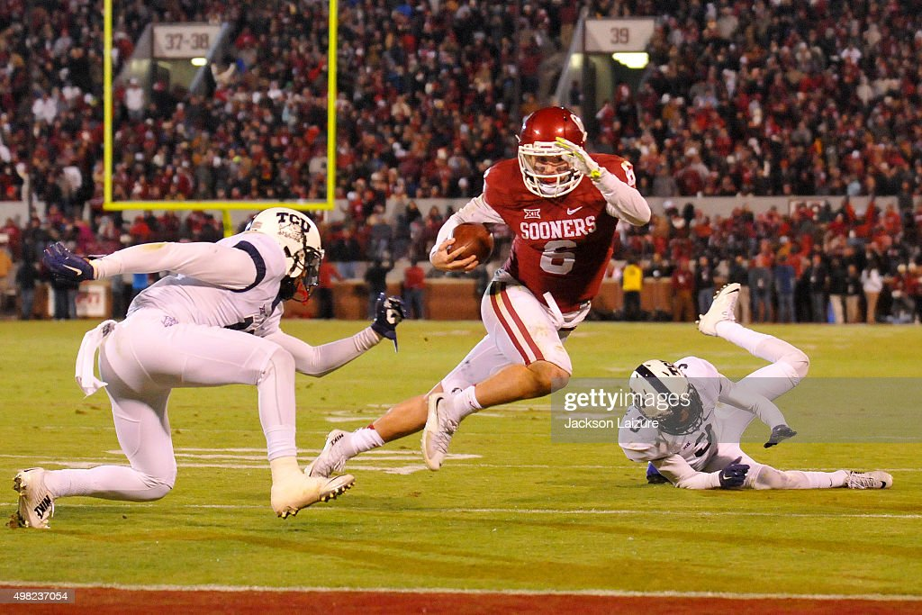 Quarterback Baker Mayfield #6 of the Oklahoma Sooners tries to avoid tackles from cornerbacks Corry O'Meally #3 and Nick Orr #18 of the TCU Horned Frogs on November 21, 2015 at the Gaylord Family Oklahoma Memorial Stadium in Norman, Oklahoma.