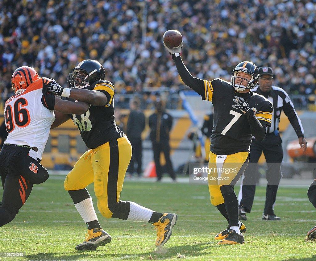 Quarterback Ben Roethlisberger of the Pittsburgh Steelers passes as offensive lineman Kelvin Beachum #68 blocks defensive lineman Carlos Dunlap #96 of the Cincinnati Bengals at Heinz Field on December 23, 2012 in Pittsburgh, Pennsylvania. The Bengals defeated the Steelers 13-10.