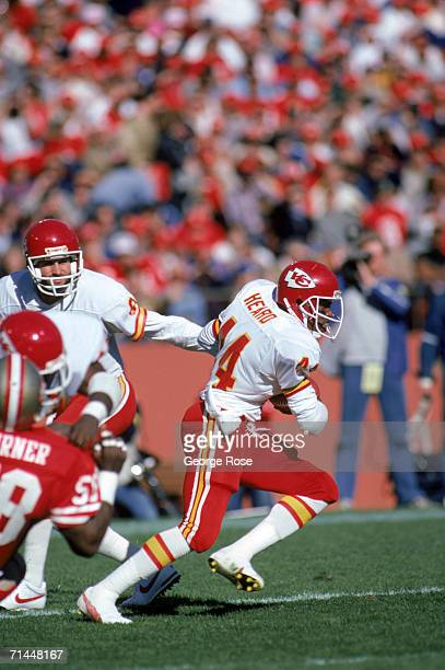 Quarterback Bill Kenney hands off the ball to running back Herman Heard of the Kansas City Chiefs during a game against San Francisco 49ers at...