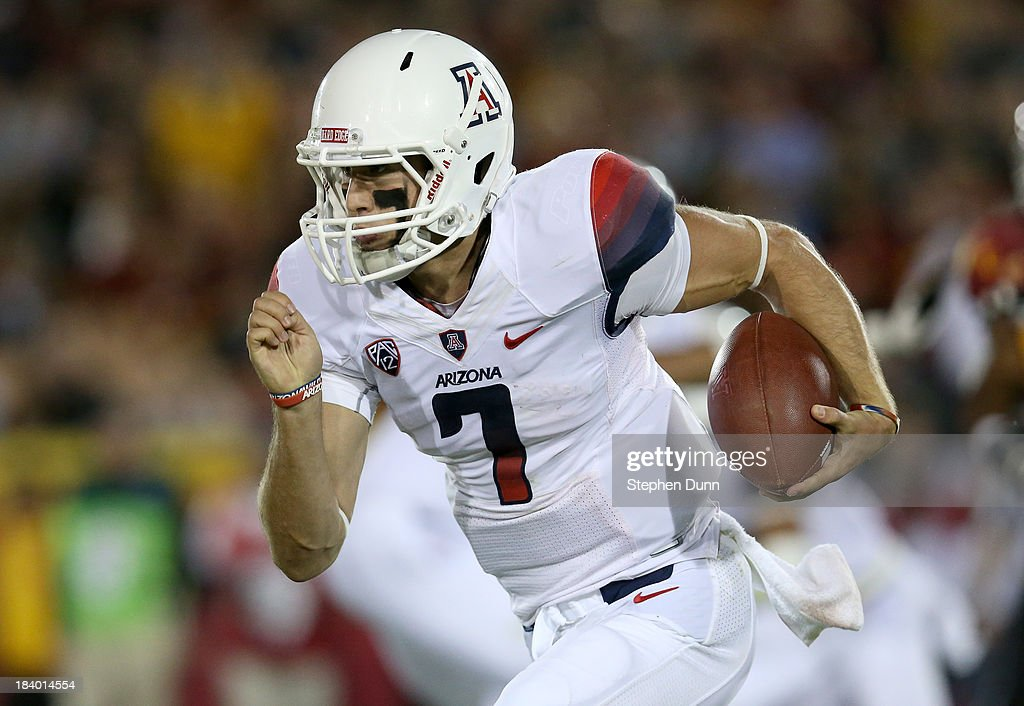 Quarterback B.J. Denker #7 of the Arizona Wildcats runs with the ball against the USC Trojans at Los Angeles Coliseum on October 10, 2013 in Los Angeles, California. USC won 38-31.