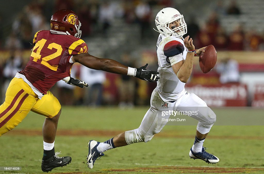 Quarterback B.J. Denker #7 of the Arizona Wildcats scrambles away from linebacker Devon Kennard #42 of the USC Trojans at Los Angeles Coliseum on October 10, 2013 in Los Angeles, California. USC won 38-31.