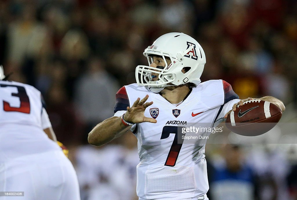 Quarterback B.J. Denker #7 of the Arizona Wildcats throws a pass against the USC Trojans at Los Angeles Coliseum on October 10, 2013 in Los Angeles, California.