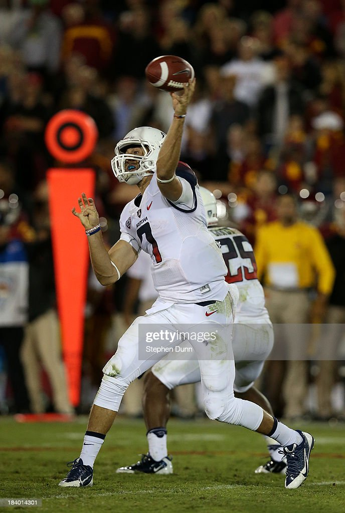 Quarterback B.J. Denker #7 of the Arizona Wildcats throws a pass against the USC Trojans at Los Angeles Coliseum on October 10, 2013 in Los Angeles, California. USC won 38-31.