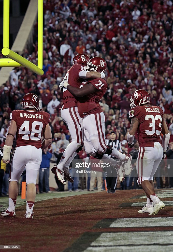 Quarterback Blake Bell #10 and offensive linesman Tyrus Thompson #71 of the Oklahoma Sooners celebrate a touchdown against the Oklahoma State Cowboys November 24, 2012 at Gaylord Family-Oklahoma Memorial Stadium in Norman, Oklahoma. Oklahoma defeated Oklahoma State 51-48 in overtime.