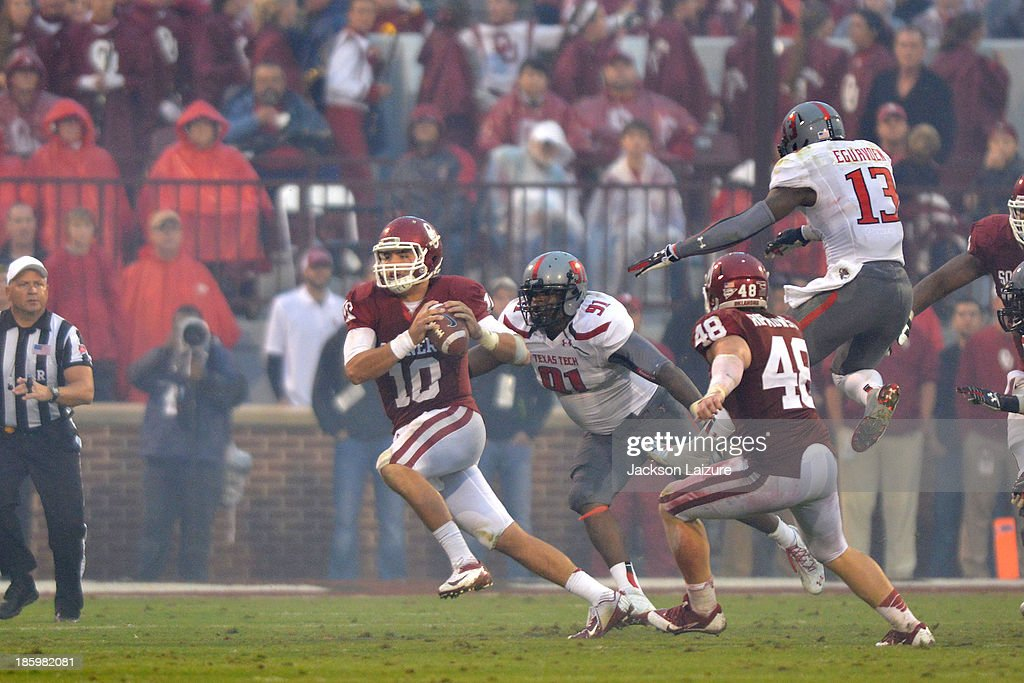 Quarterback Blake Bell #10 of the Oklahoma Sooners completes a pass on the run during the second half of their win while being pressured by defensive lineman Kerry Hyder #91 of the Texas Tech Red Raiders on October 26, 2013 at Gaylord Family Oklahoma Memorial Stadium in Norman, Oklahoma.