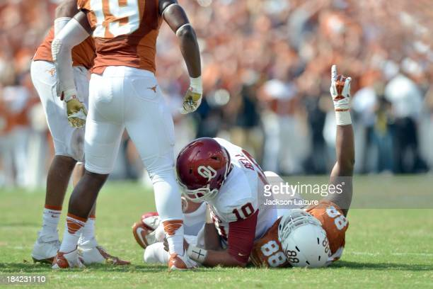 Quarterback Blake Bell of the Oklahoma Sooners is sacked by defensive end Cedric Reed of the Texas Longhorns on a fourth down in the fourth quarter...